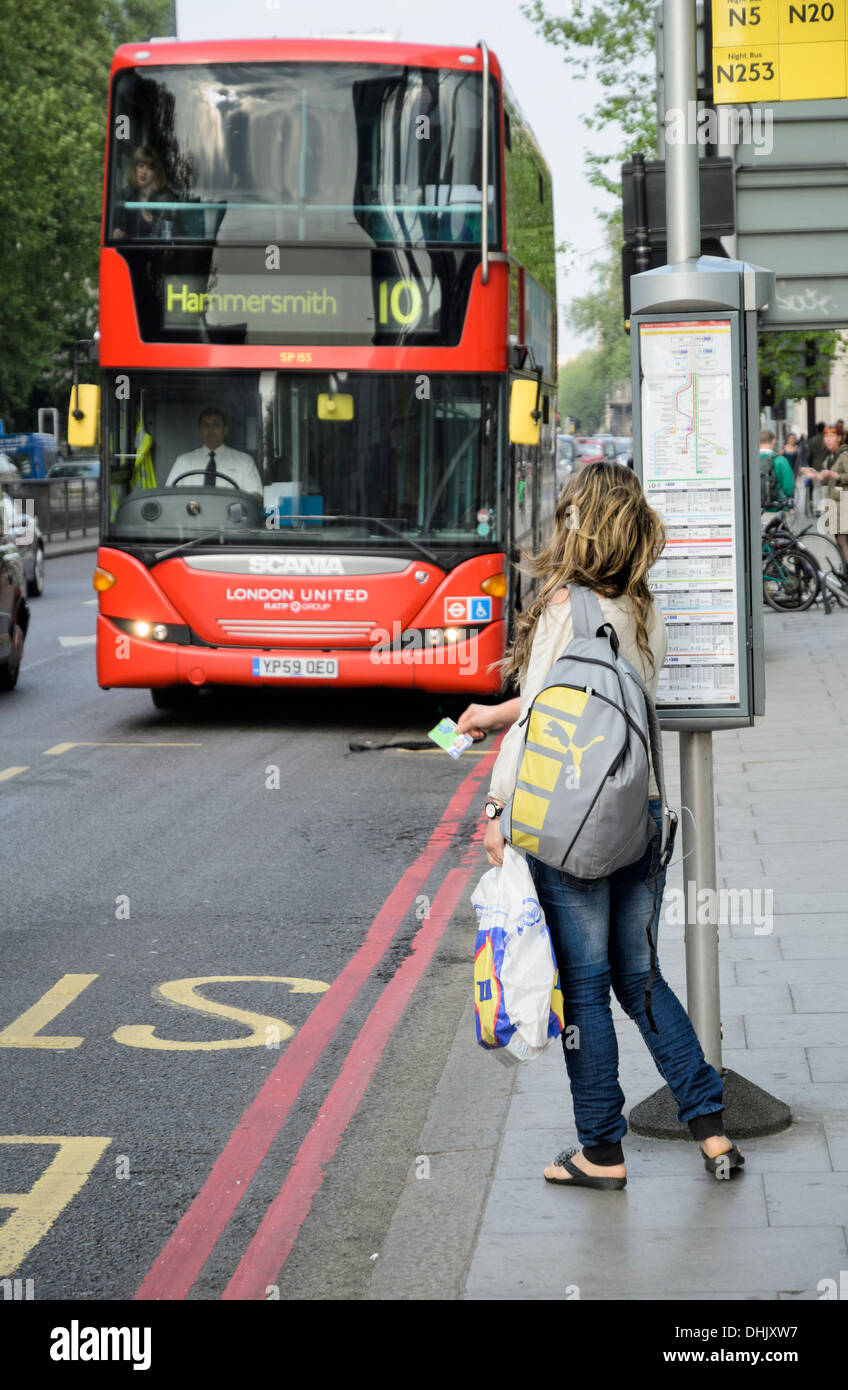 Waiting for the bus: Young female passenger at a London bus stop holds out her ticket or pass to signal for the bus to stop; woman commuter; red bus - Stock Image
