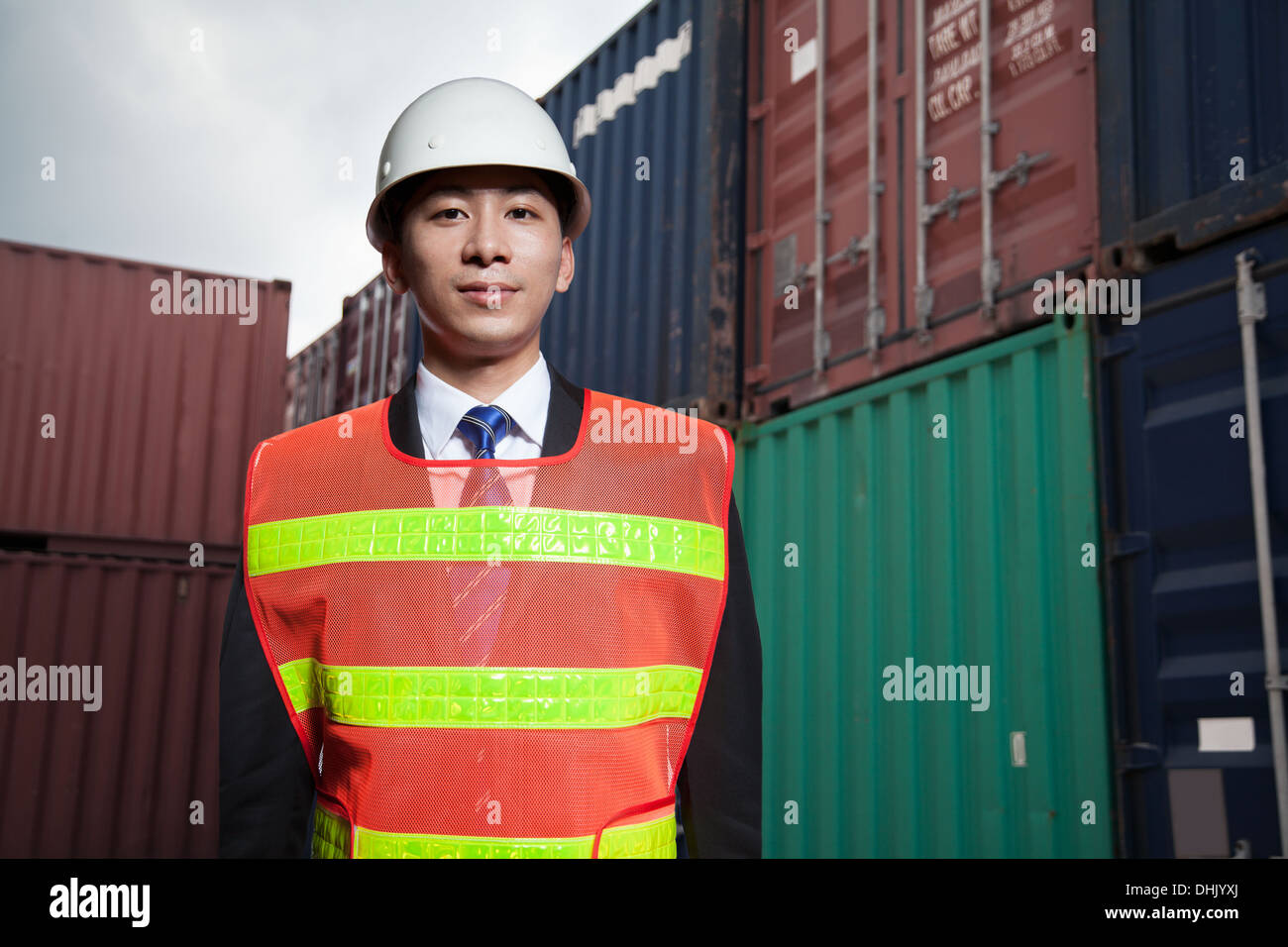 Portrait of proud engineer in protective workwear standing in a shipping yard - Stock Photo