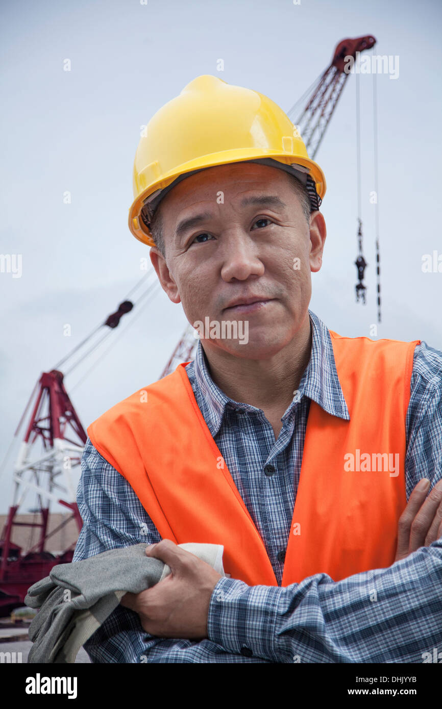 Portrait of proud worker with arms crossed in protective workwear outside in a shipping yard, crane in the background - Stock Image