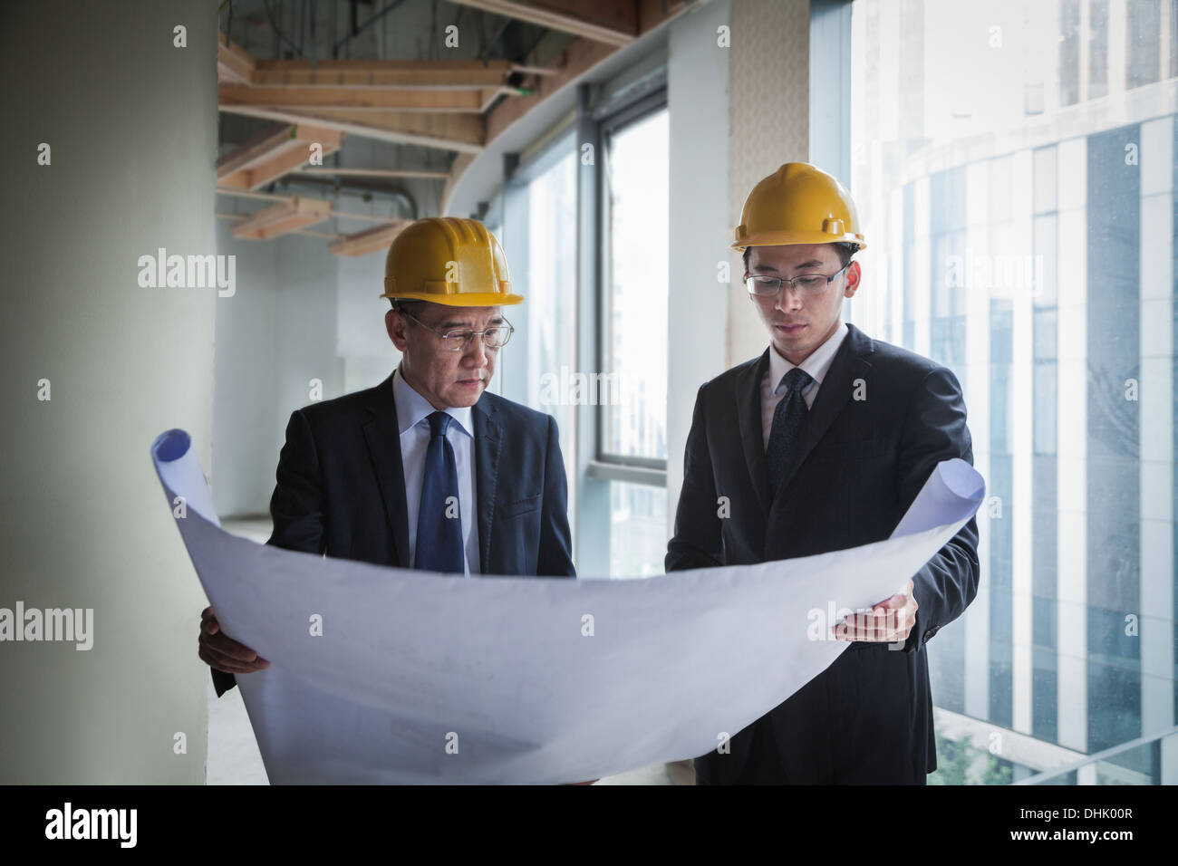Two architects in hardhats examining a blueprint in an office building - Stock Image