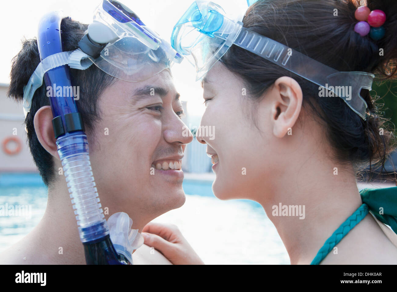Smiling couple face to face in snorkeling gear in the pool - Stock Image