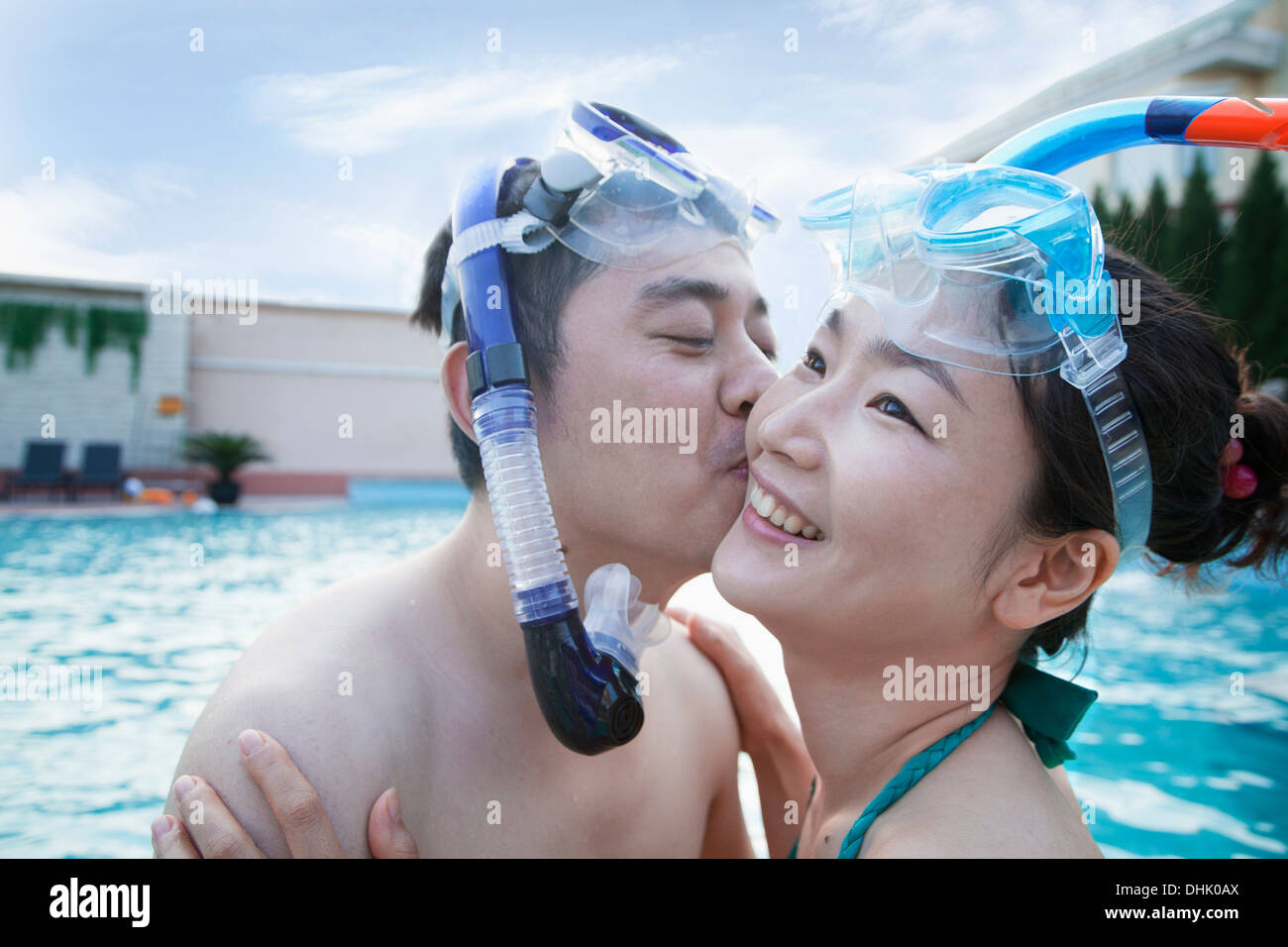 Smiling couple kissing on the cheek wearing snorkeling gear in the pool - Stock Image