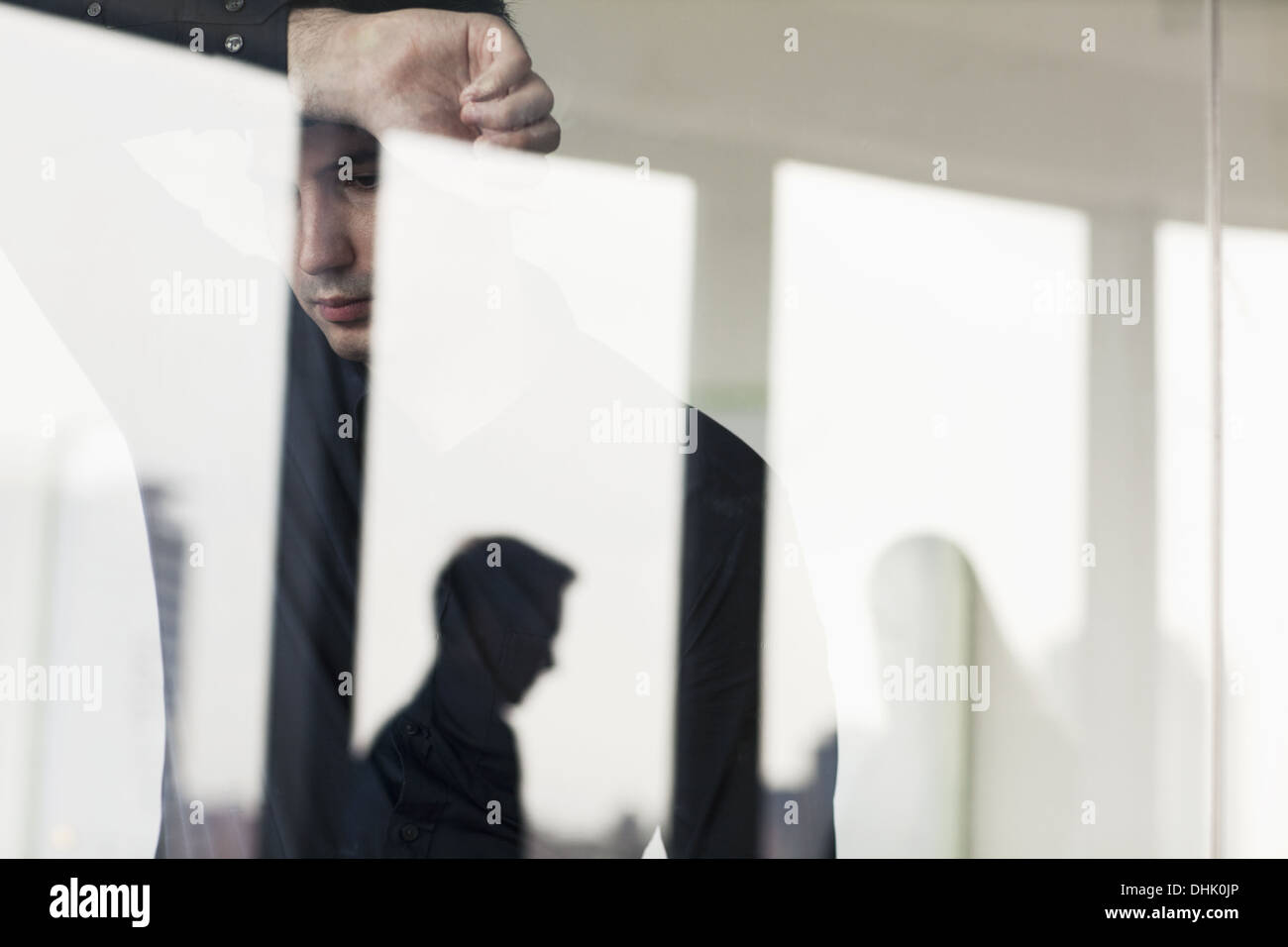 Overworked businessman with arm raised leaning on the other side of a glass wall - Stock Image