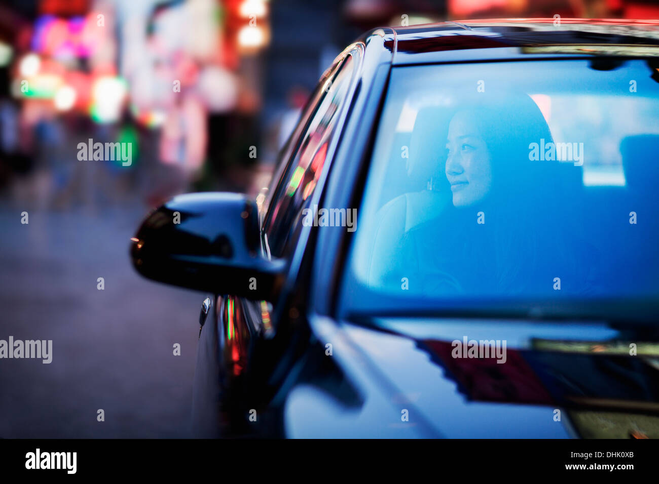 Serene woman looking through car window at the city nightlife - Stock Image