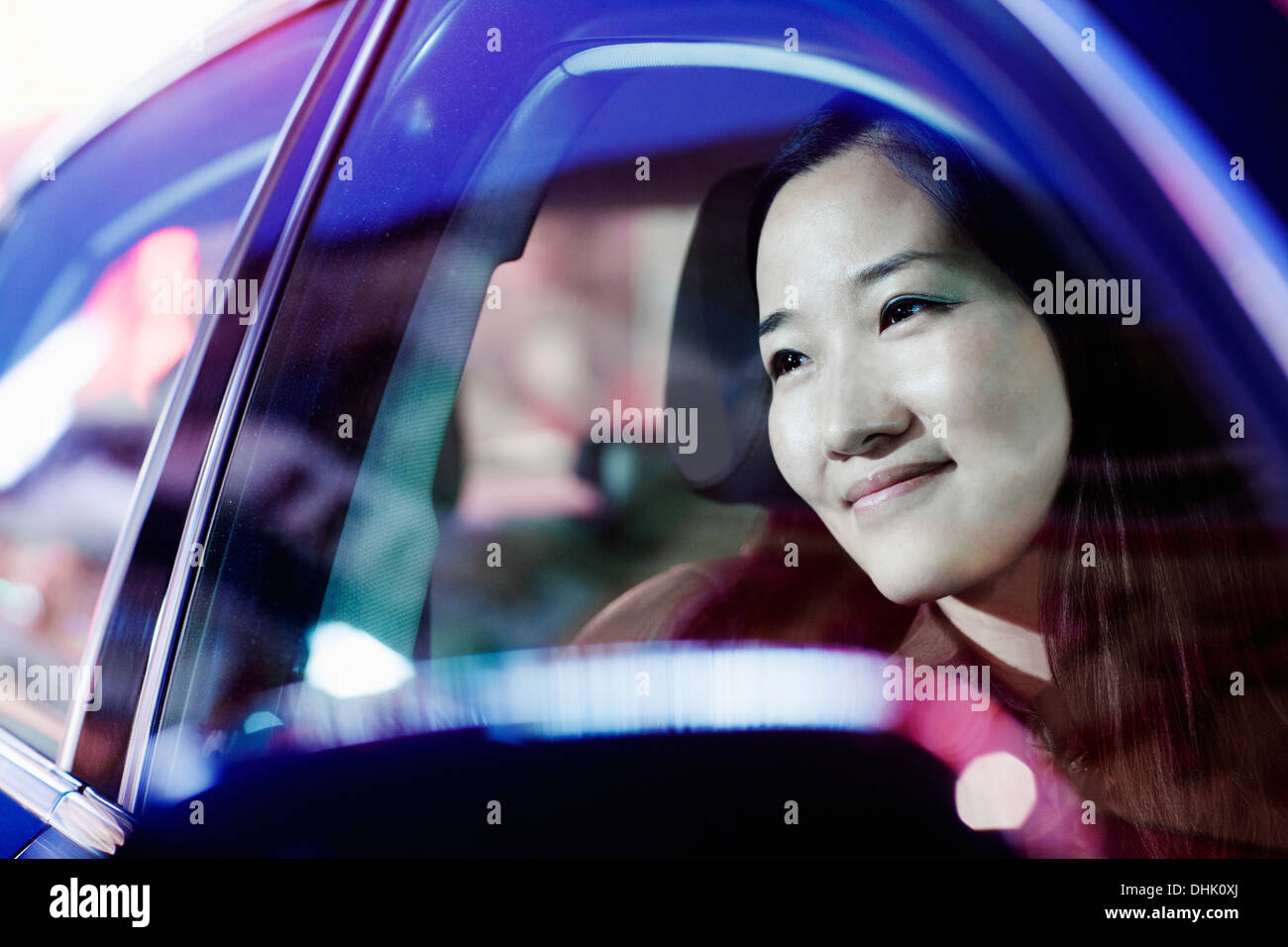 Smiling woman looking through car window at the city nightlife, reflected lights Stock Photo