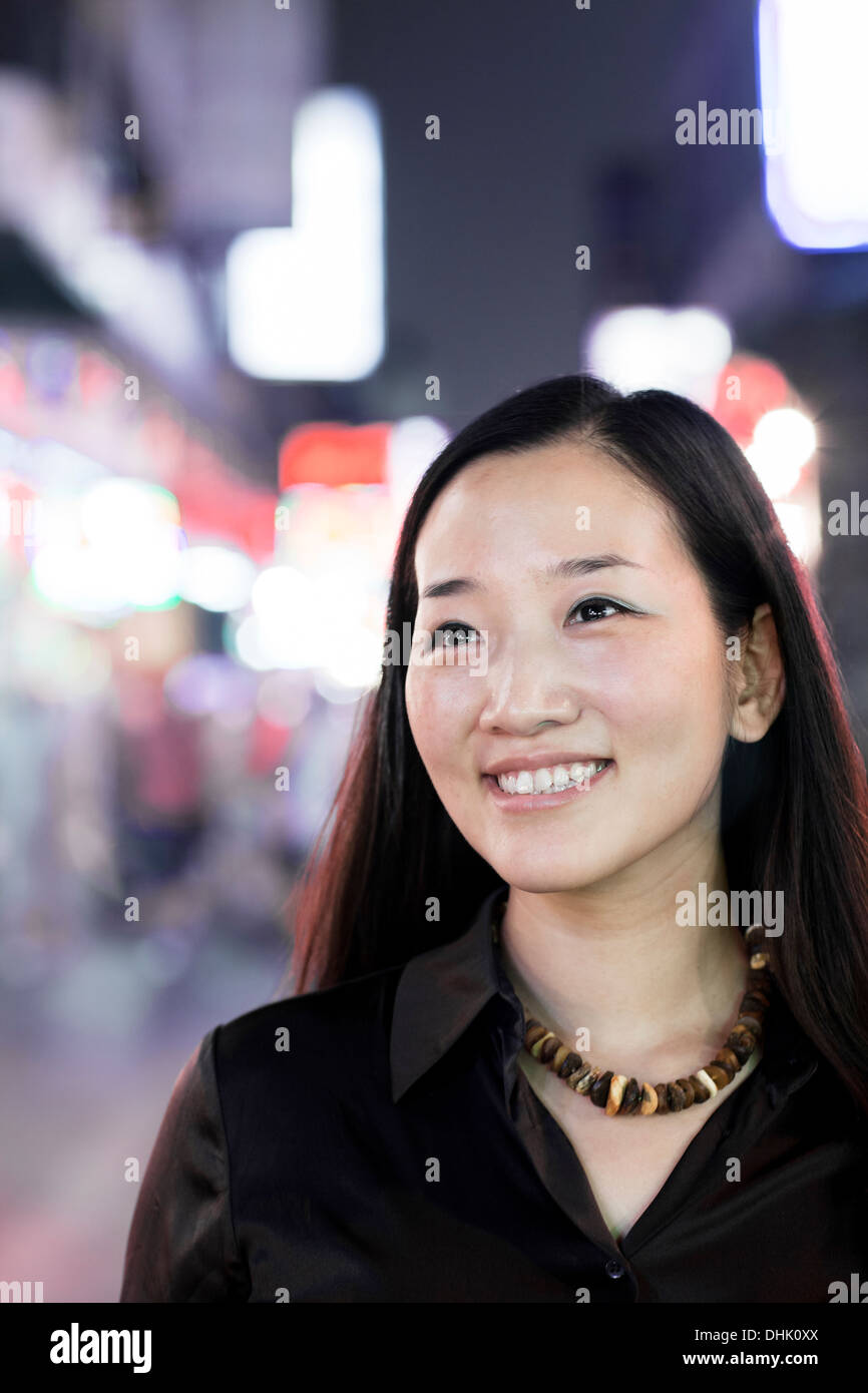 Smiling woman out at night in the city, portrait - Stock Image
