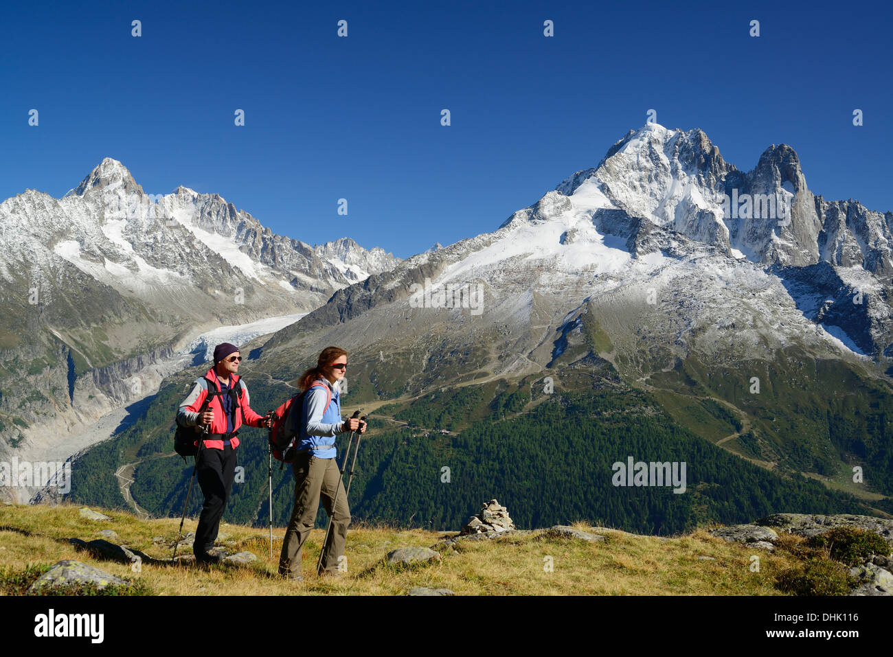 Woman and man hiking with view to Aiguille du Chardonnet, Aiguille d' Argentiere, Aiguille Verte and Grand Dru, Mont Blanc range - Stock Image