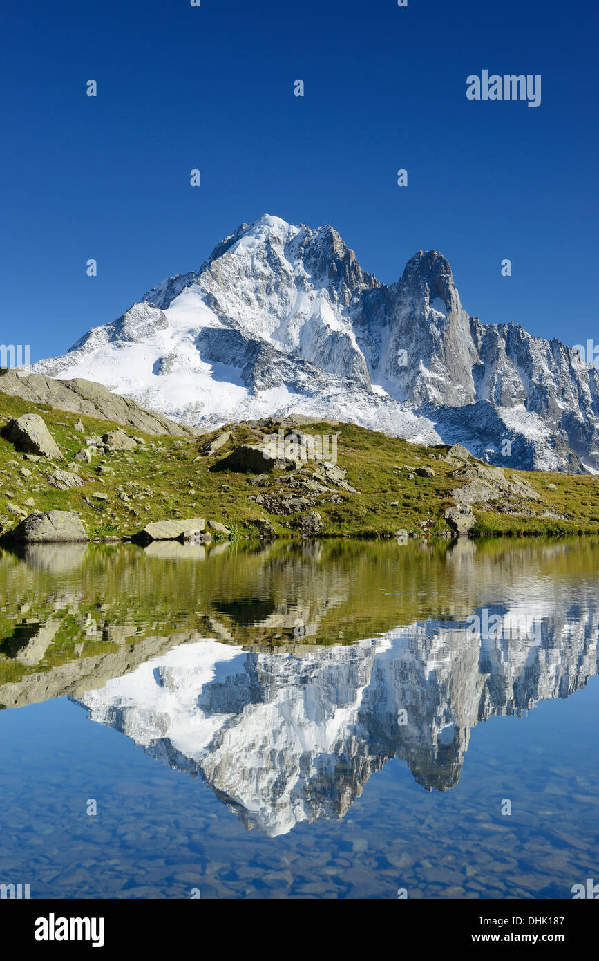 Mont Blanc range with Aiguille Verte and Grand Dru reflecting in a mountain lake, Mont Blanc range, Chamonix, Savoy, France - Stock Image