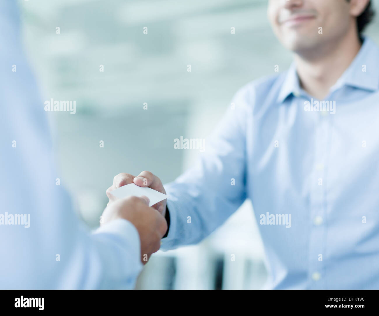 Close up of two businessmen exchanging business cards - Stock Image