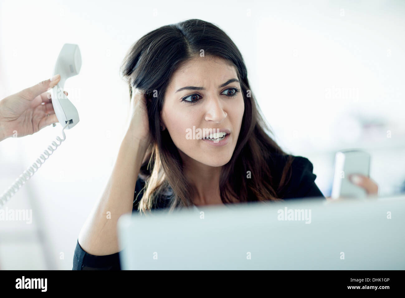 Overworked young businesswoman answering phones - Stock Image