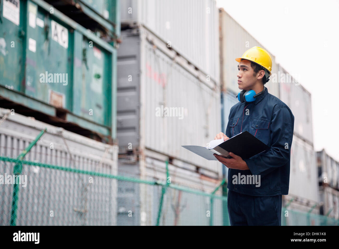 Young worker in protective work wear examining cargo in a shipping yard - Stock Image