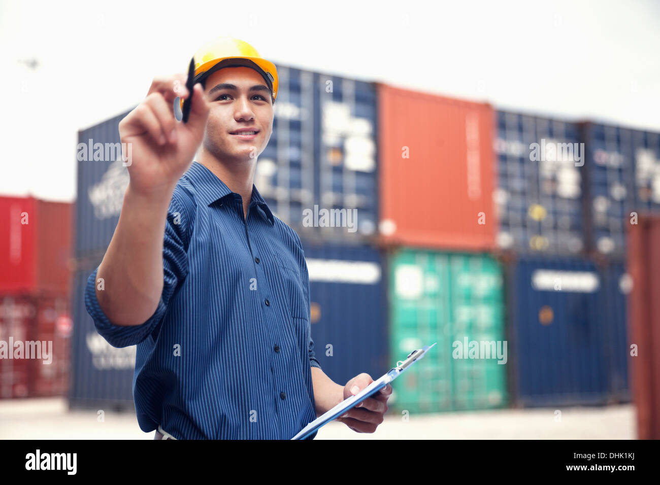 Smiling young engineer in protective work wear in a shipping yard examining cargo - Stock Image