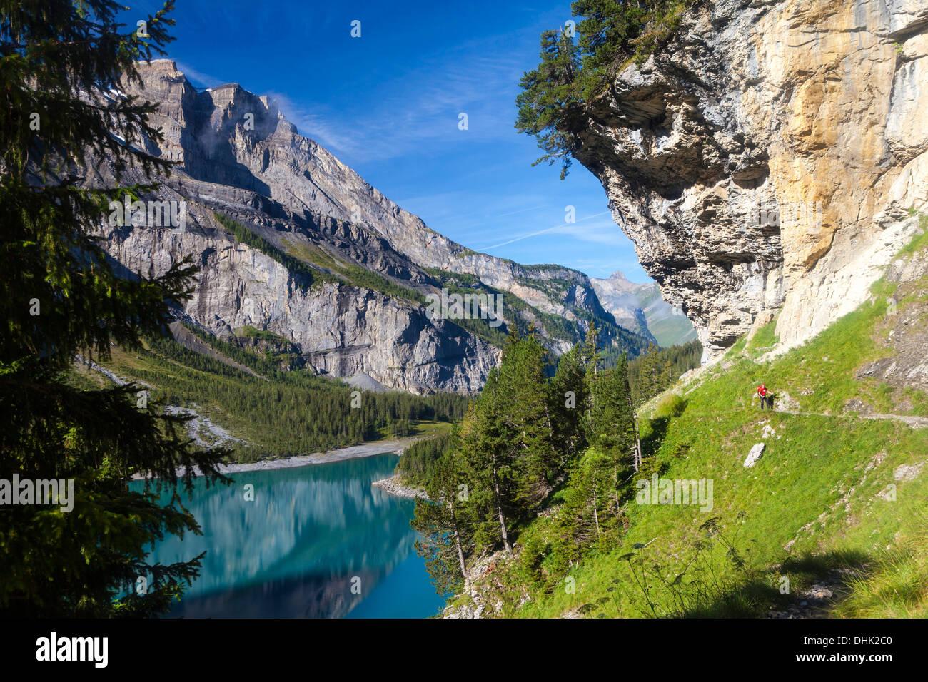A man hiking at lake Oeschinen, Bernese Oberland, Canton of Bern, Switzerland - Stock Image