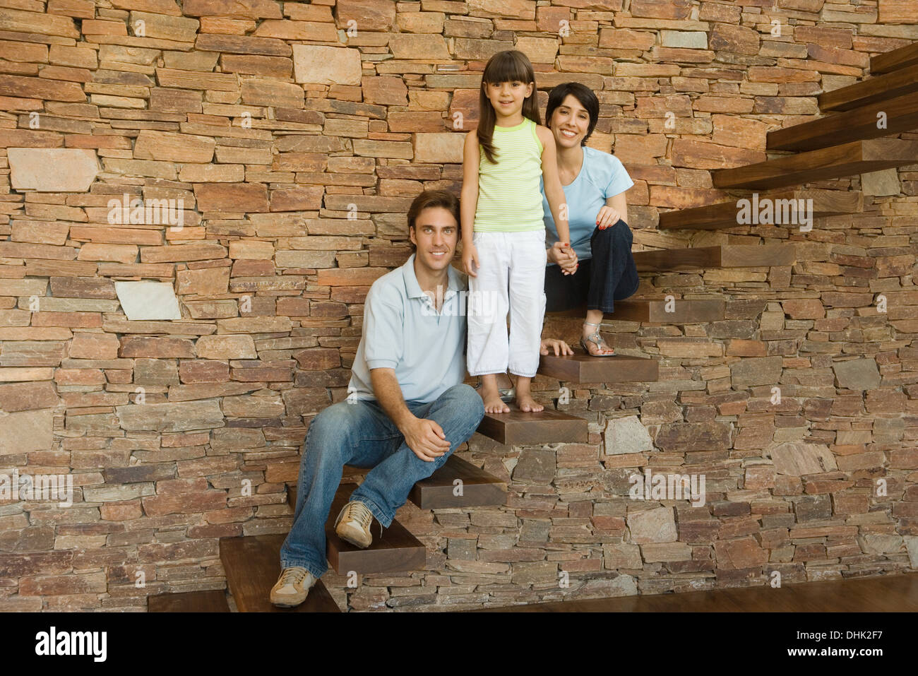 Girl and parents on stairs - Stock Image