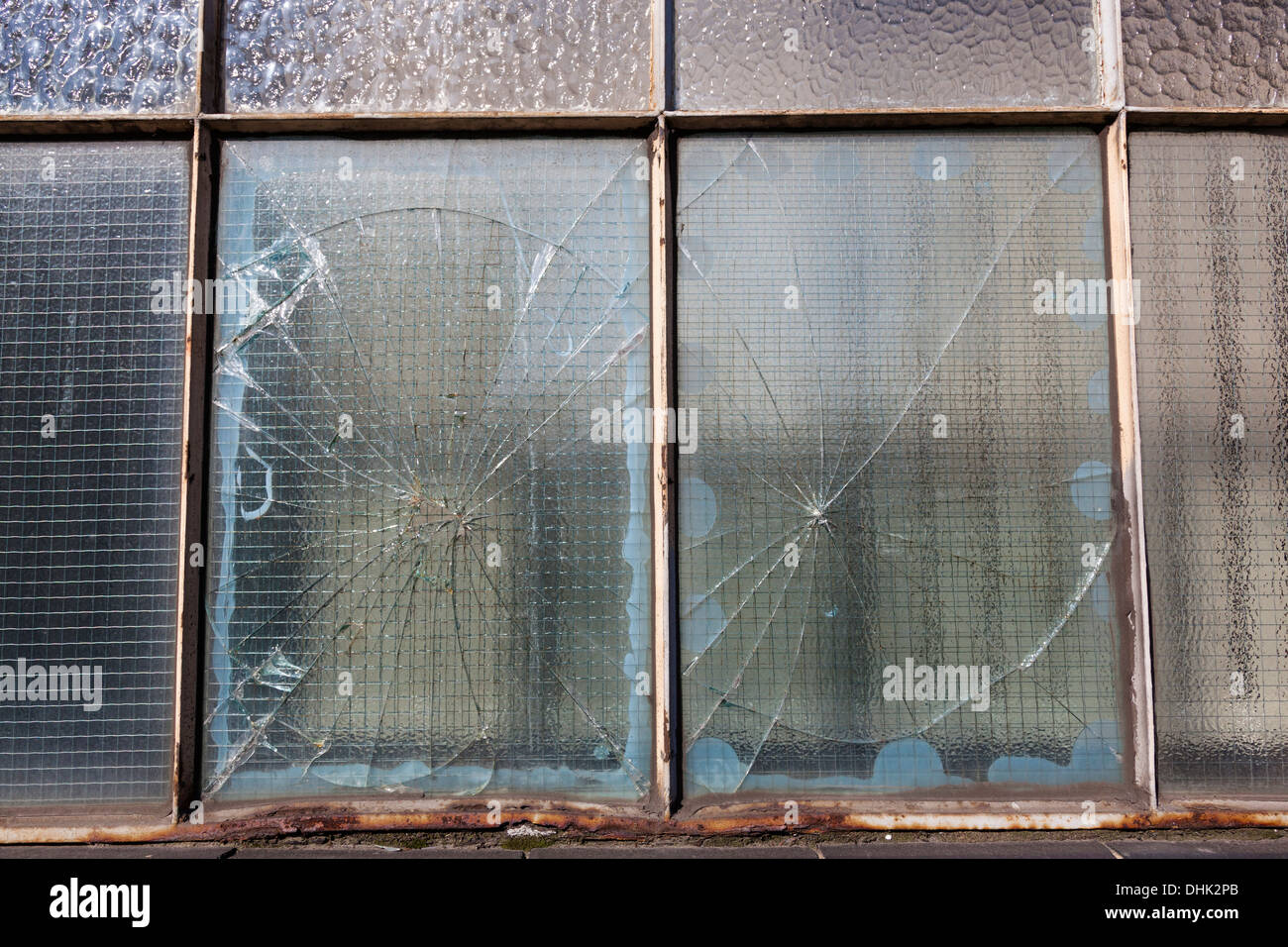Close-up of a rusty metal framed window with smashed wired glass ...