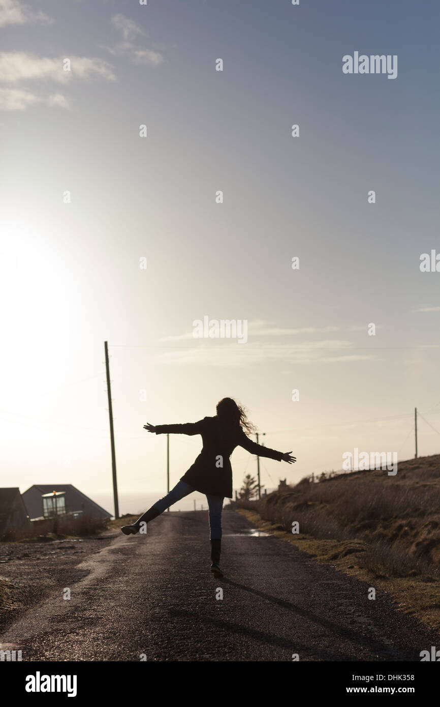 Silhouette of a girl doing a star jump on a remote road in the Scottish highlands. - Stock Image
