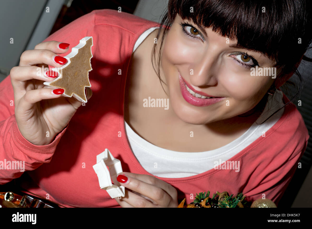Beautiful funny woman cutting gingerbread shapes from dough. Cookie cutters in hands. - Stock Image