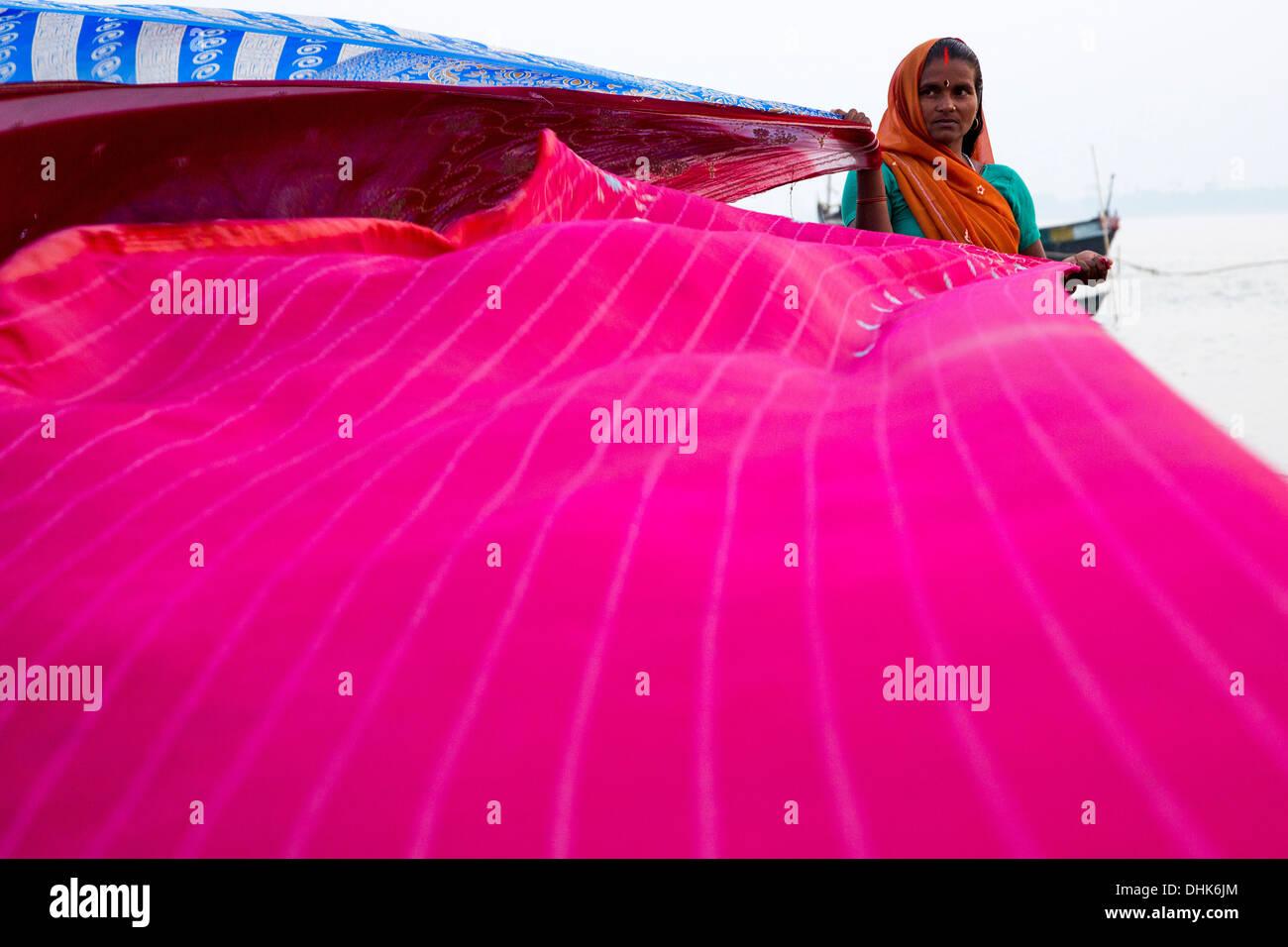 Woman dries sari cloths on banks of Ganges river, Simaria, Bihar, India - Stock Image