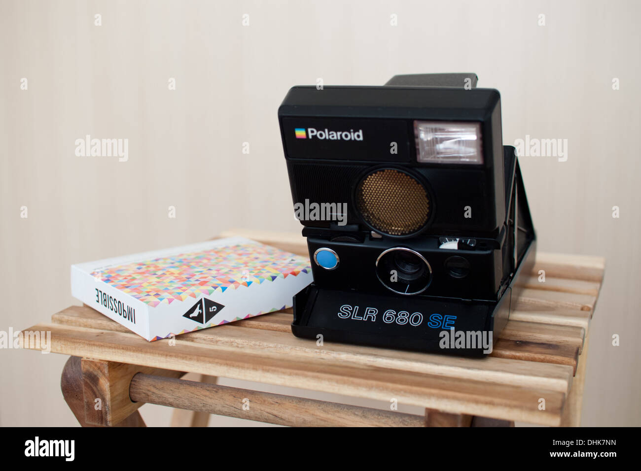 A Polaroid SLR 680 SE (Special Edition) camera and Impossible x Pigeonhole PX 680 Color Protection instant film. - Stock Image
