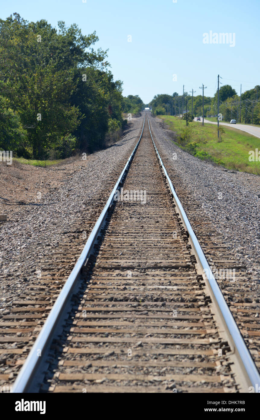 Long straight American train rail track disappears into the distance - Stock Image