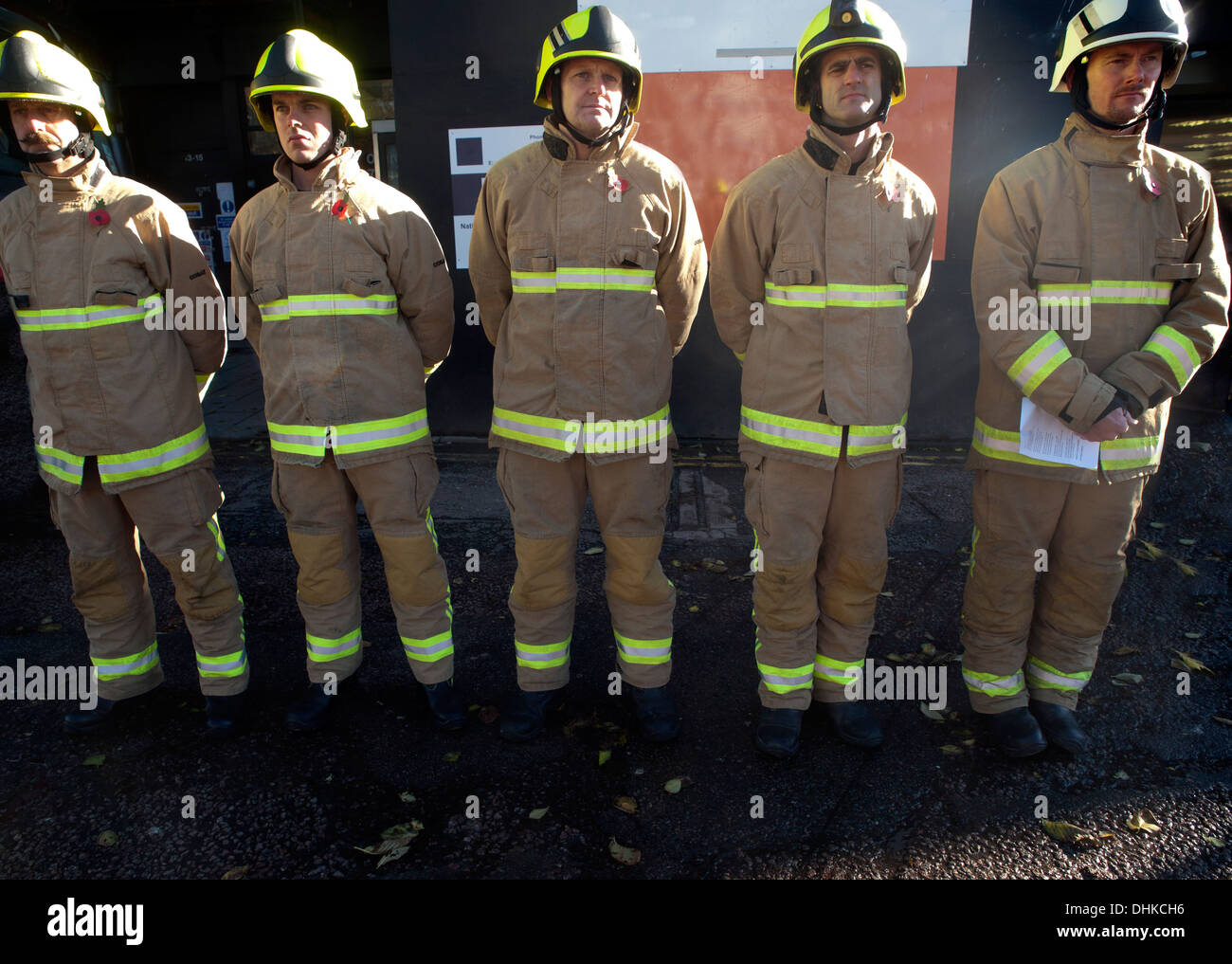 hFiremen stand to attention at a remembrance day rally - Stock Image