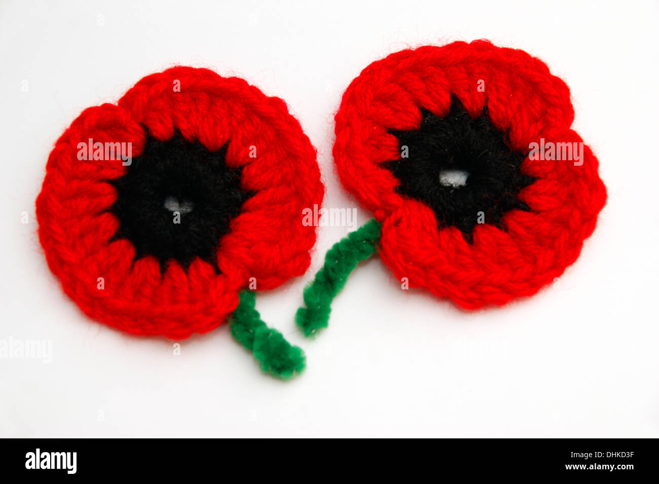 2 handmade crochet poppies the poppy emblem for remembrance & memory of the fallen in wars of the past & ongoing campaigns UK - Stock Image