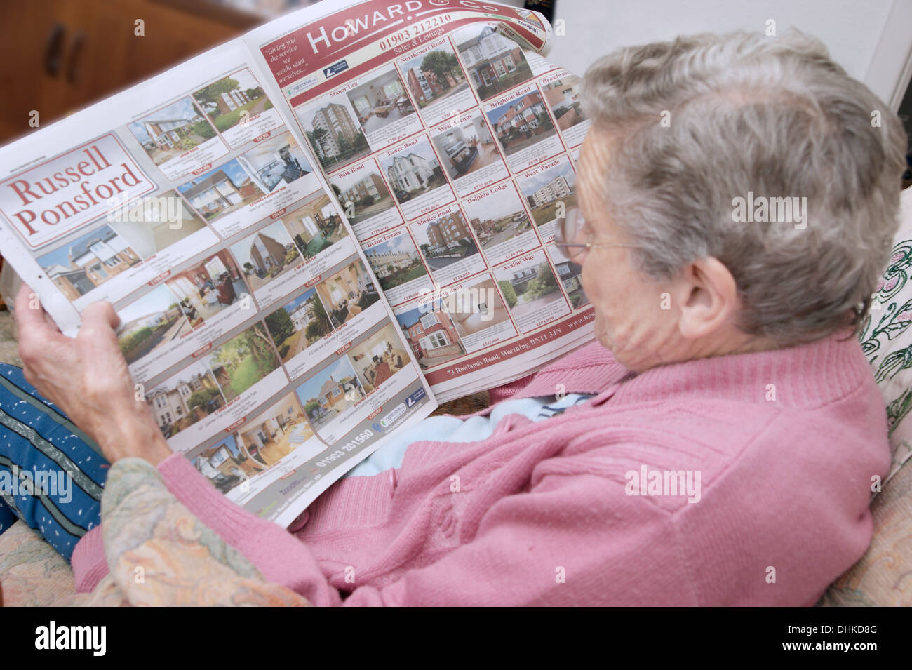 Elderly woman looking at properties on the property pages in a local paper - Stock Image