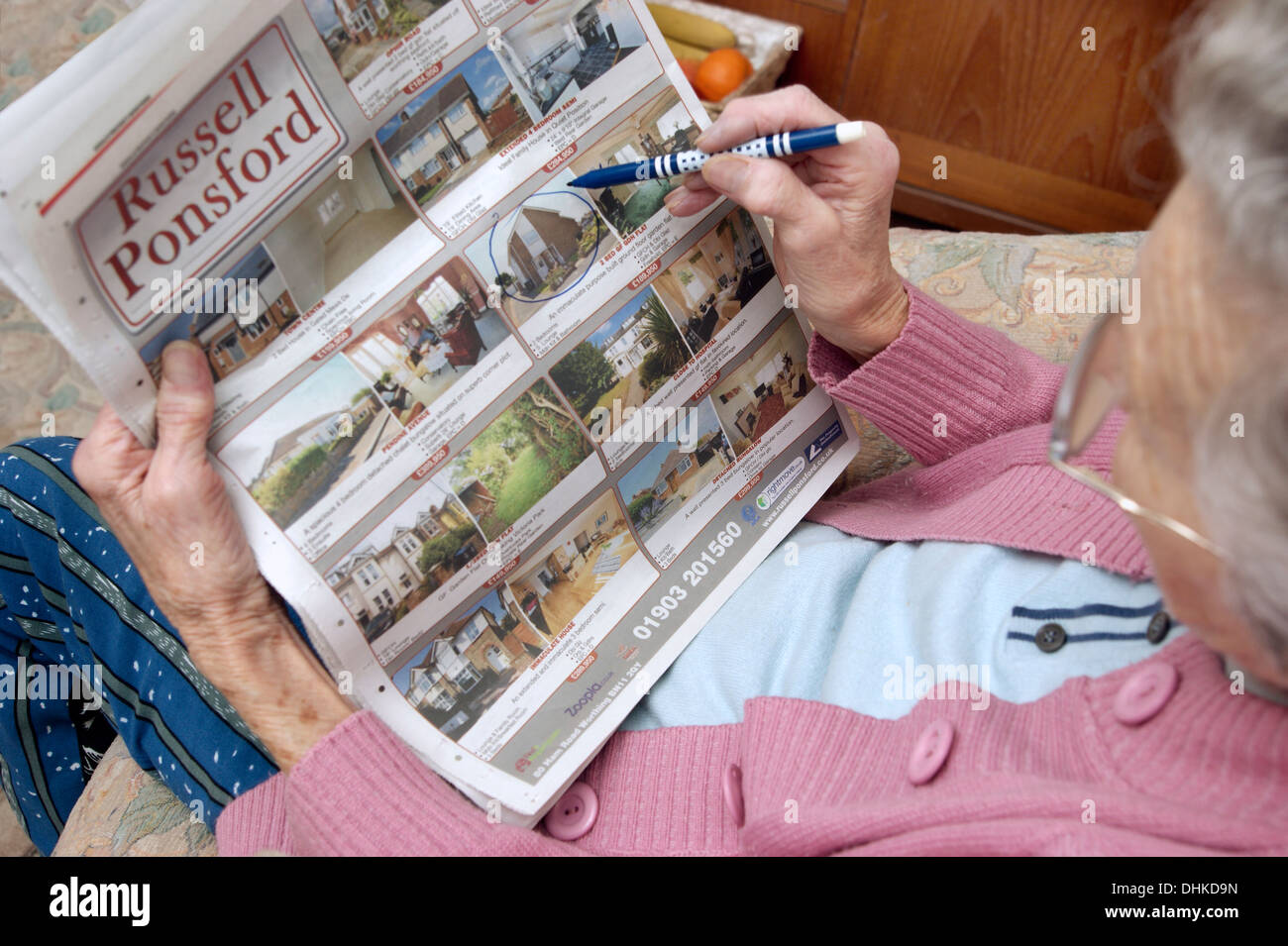 Elderly woman looking at properties on the property pages in a local paper & marking off anything interesting Stock Photo