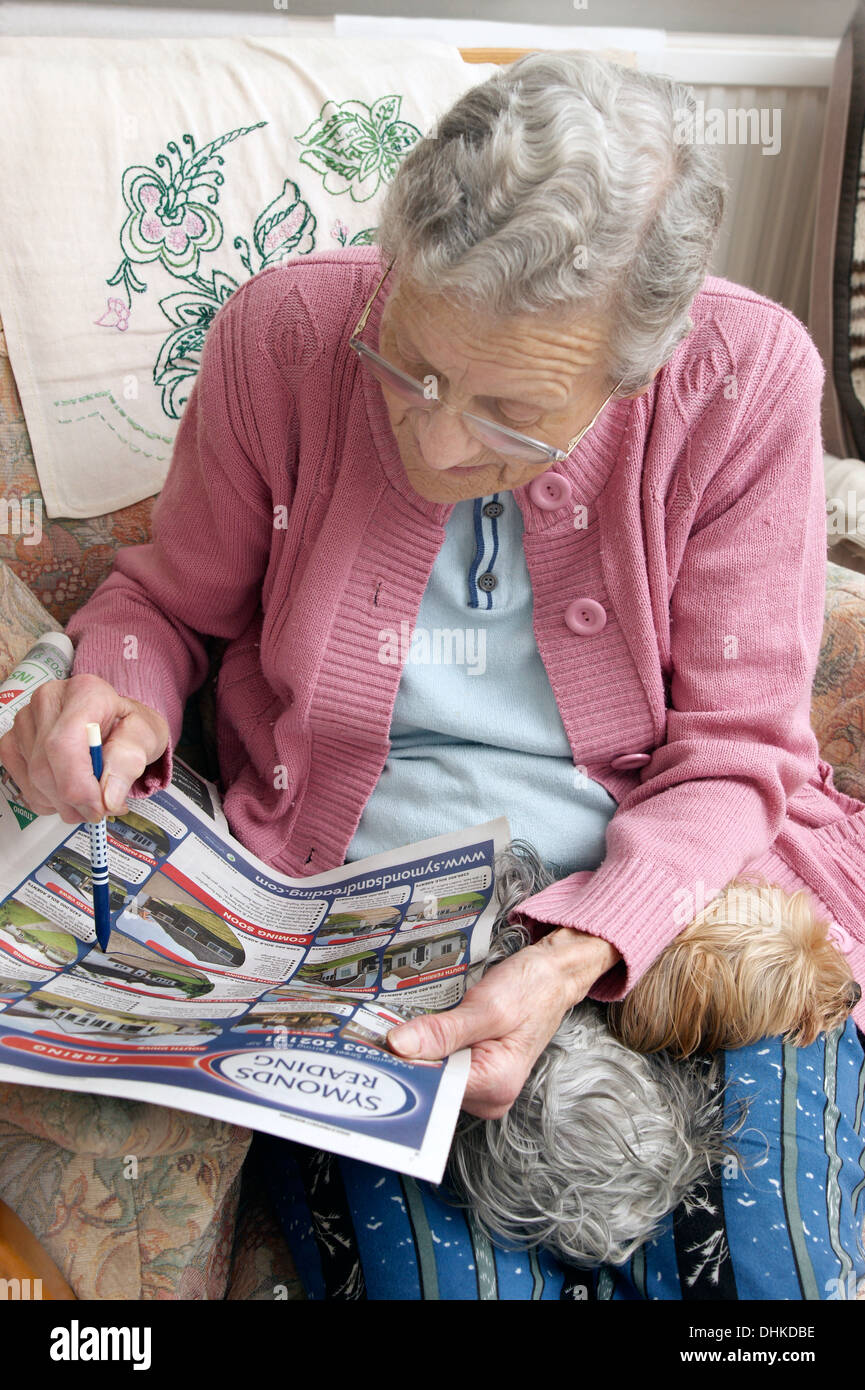 Elderly woman looking at properties on the property pages in a local paper & marking off anything interesting - Stock Image