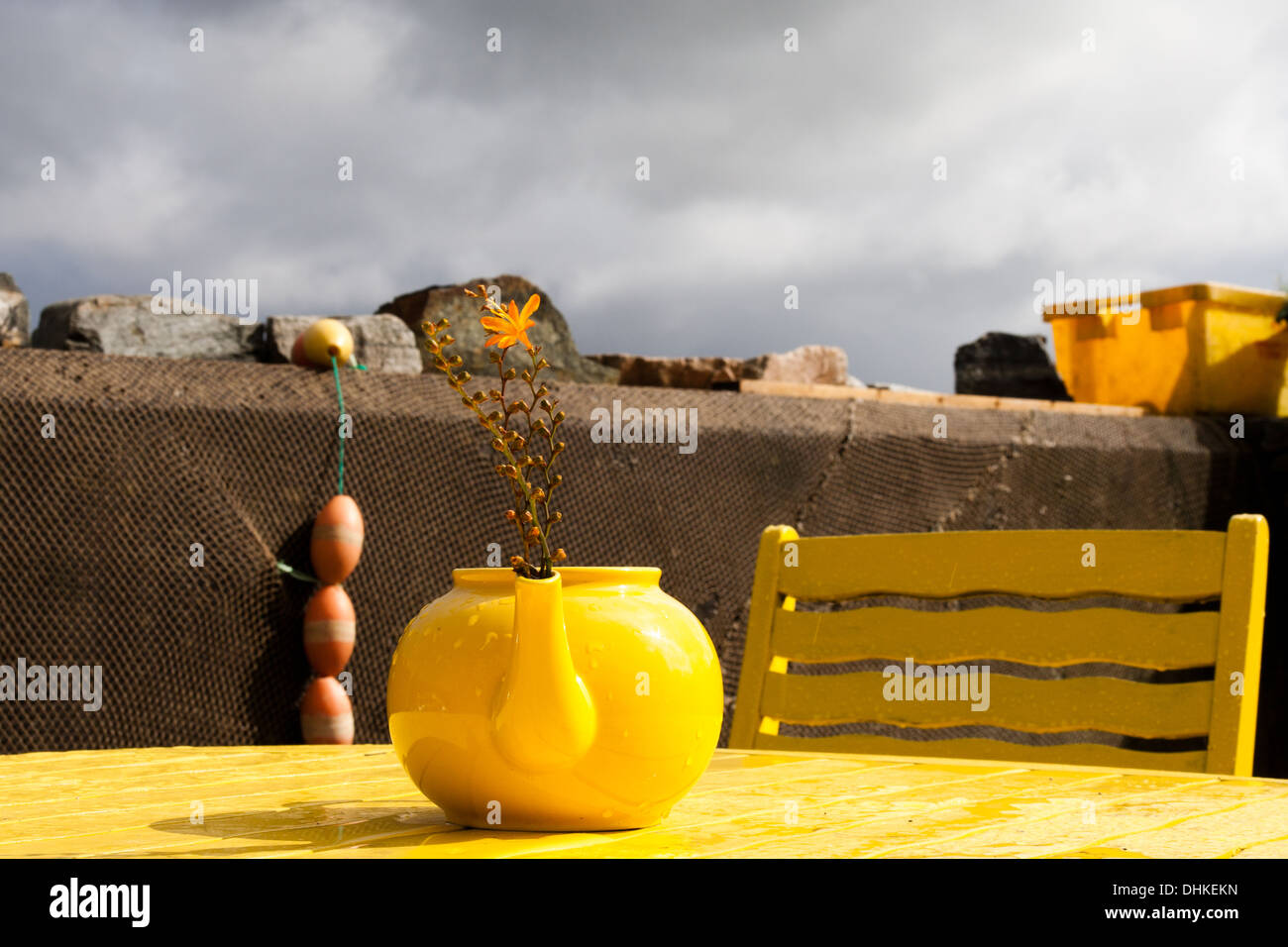 Yellow teapot chair and table at a cafe in the west of Ireland - Stock Image