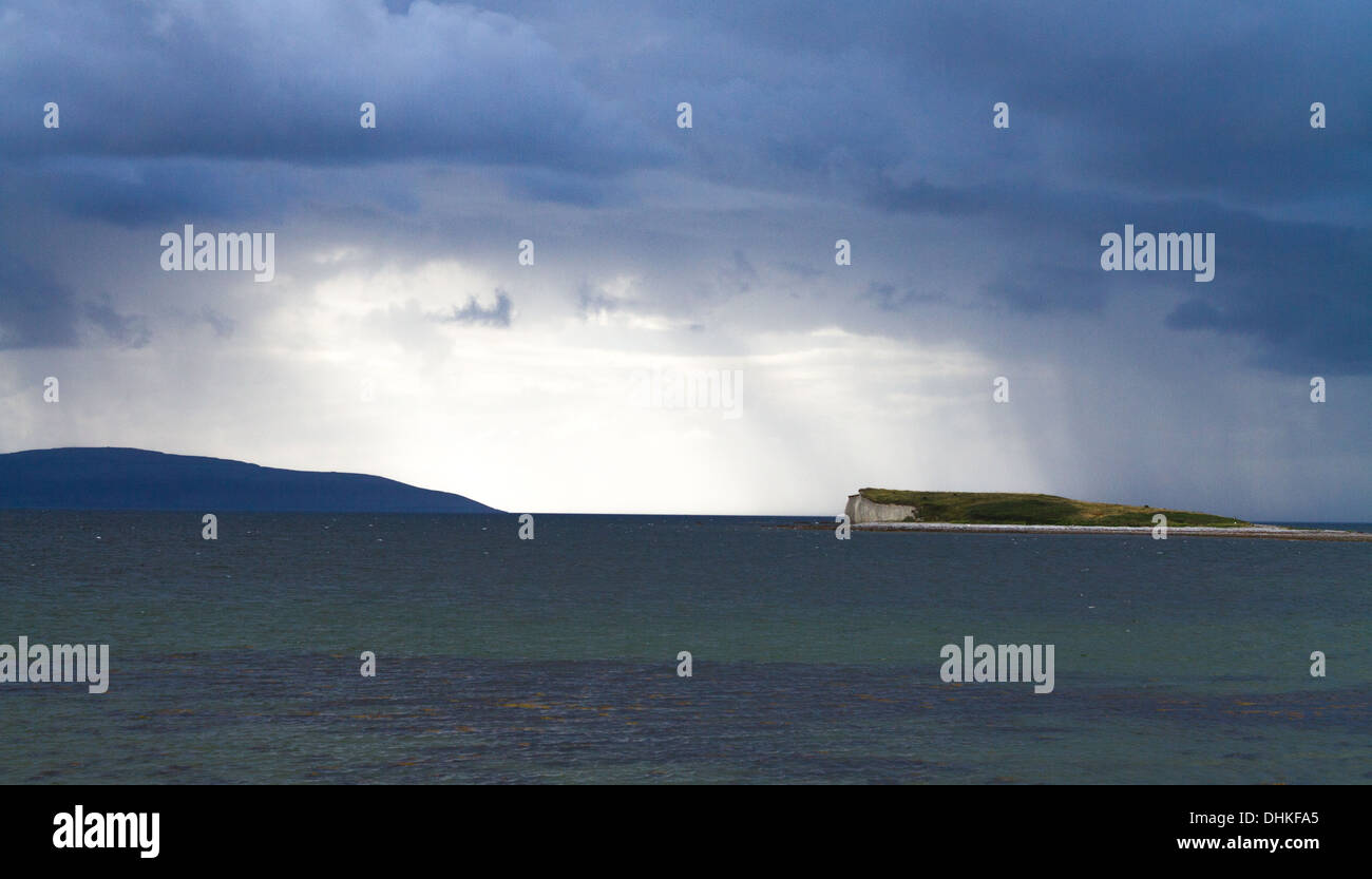 A drumlin island [Fairy Island] in Galway Bay under a moody sky - Stock Image