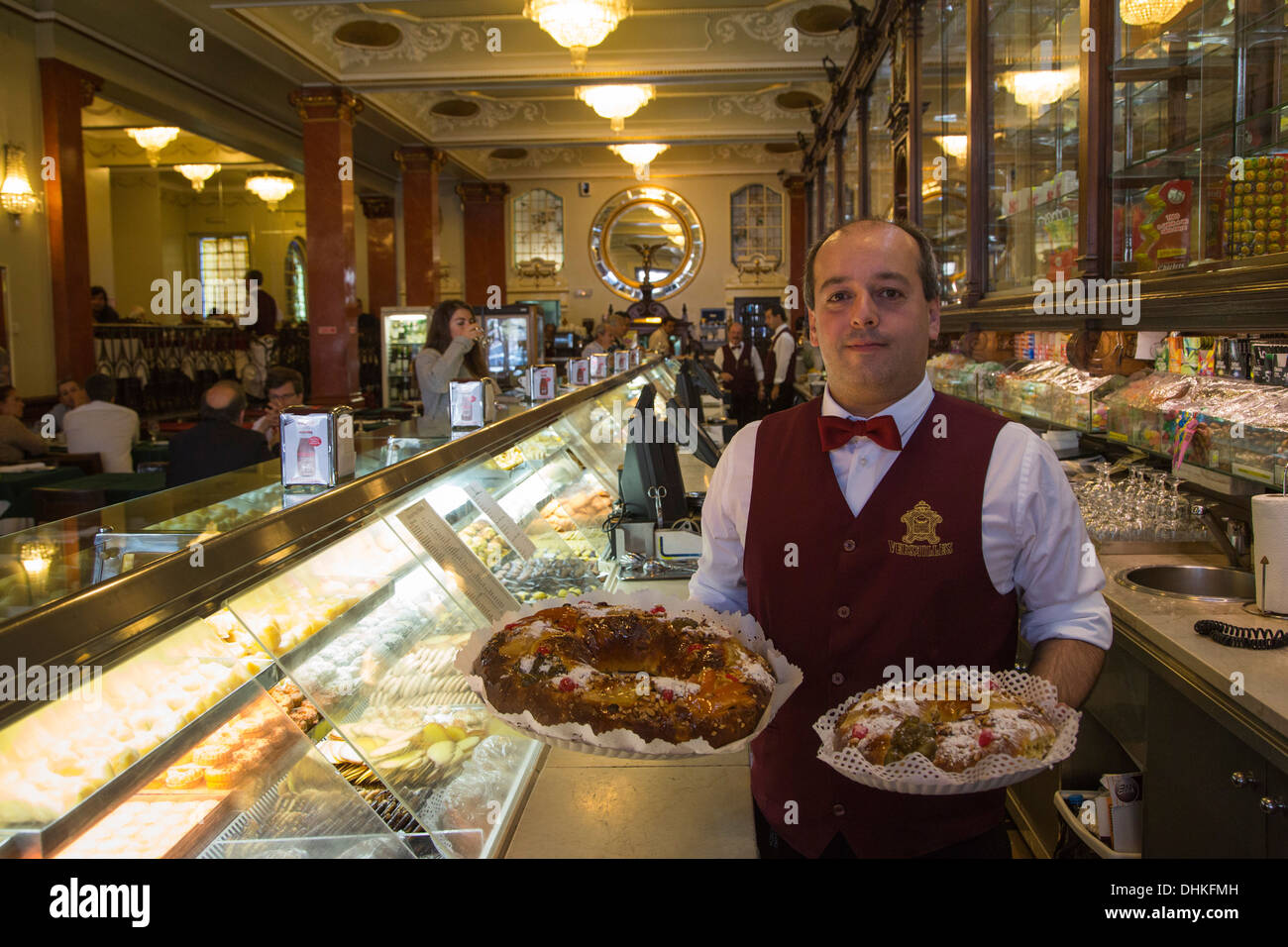 Waiter with traditional Bolo Rei cakes at Pastelaria Versailles cafe and bakery in Saldanha district, Lisbon, Lisboa, Portugal - Stock Image