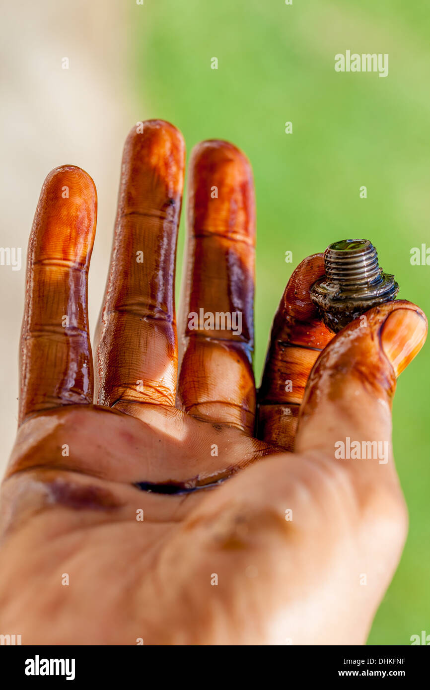 hand holding bolt and covered in car engine oil. - Stock Image