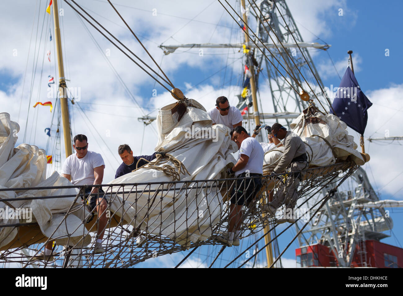 Crew members of the Brazilian Navy training vessel Cisne Branco handling her sails in The Tall Ships Races of 2013. - Stock Image