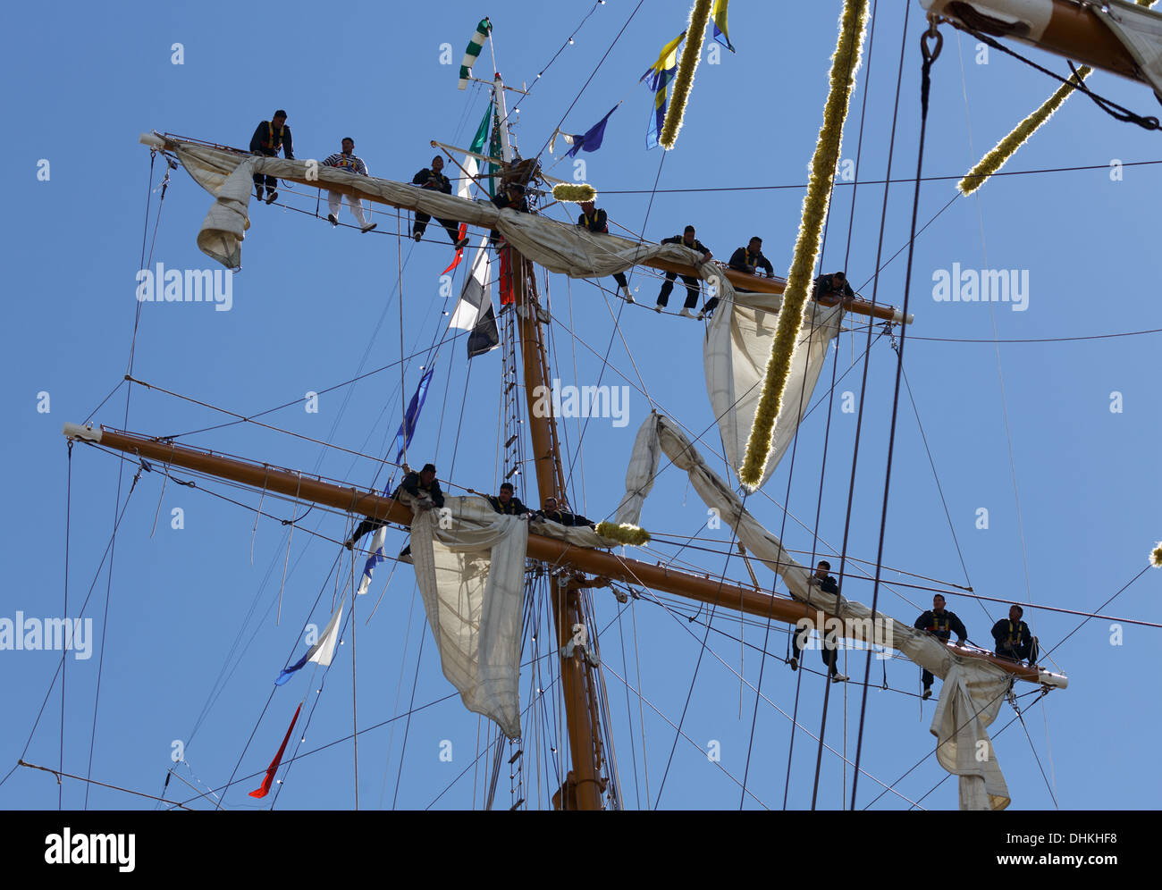 Crew members of the Mexican Navy training vessel ARM Cuauhtémoc handling her sails in The Tall Ships Races of 2013. - Stock Image