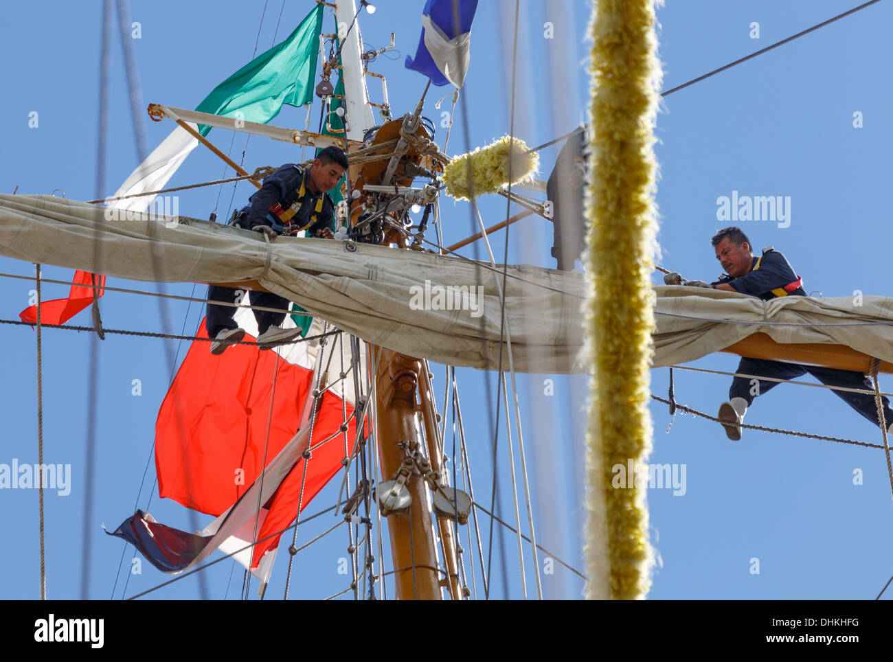 Crew members of the Mexican Navy training vessel  handling her sails in The Tall Ships Races of 2013. - Stock Image