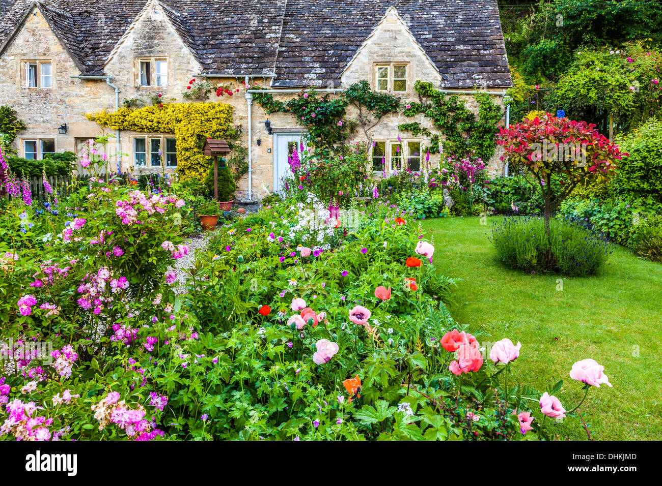 A pretty English cottage garden in the Cotswold village of Bibury in summer. - Stock Image