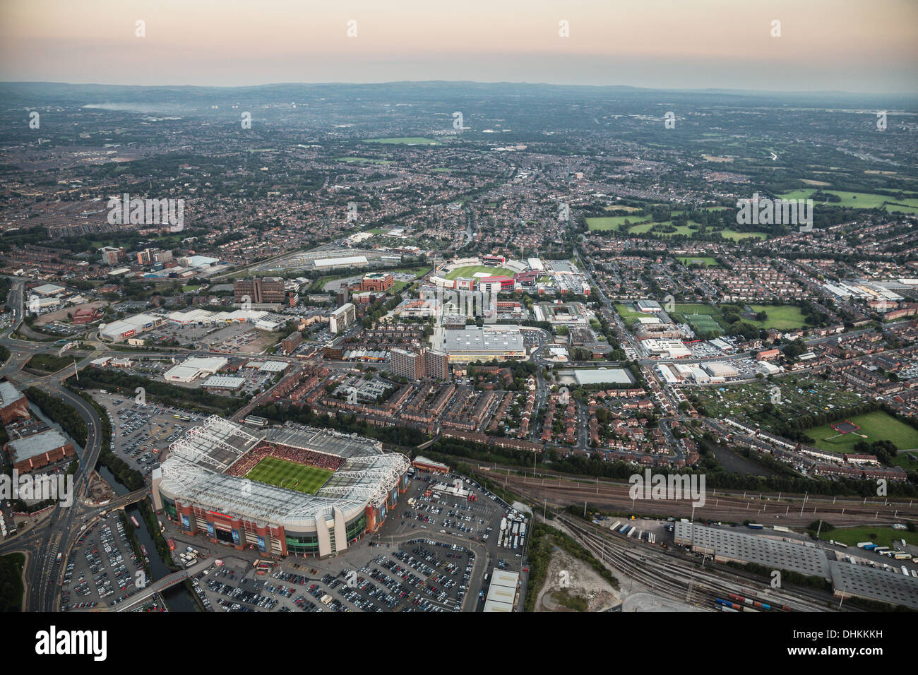 Twilight aerial view over Manchester with Old Trafford Football and Cricket Ground in the foreground. - Stock Image