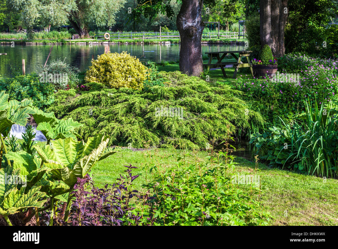 The pretty landscaped garden of the Trout Farm in the Cotswold village of Bibury in the Coln Valley. - Stock Image