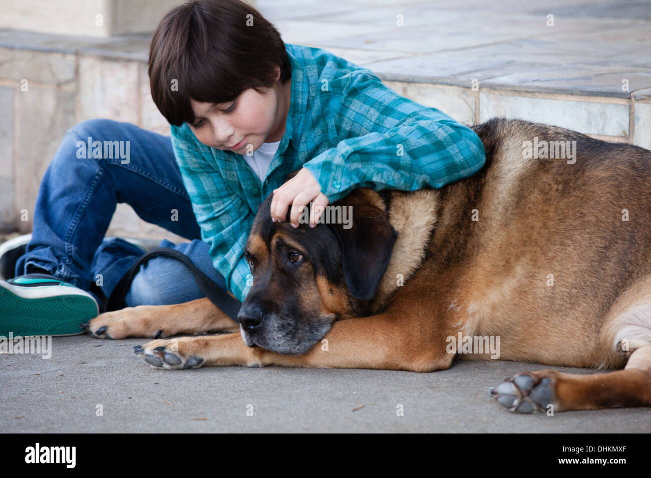 A 10 year old boy and his dog sitting down on the sidewalk - Stock Image