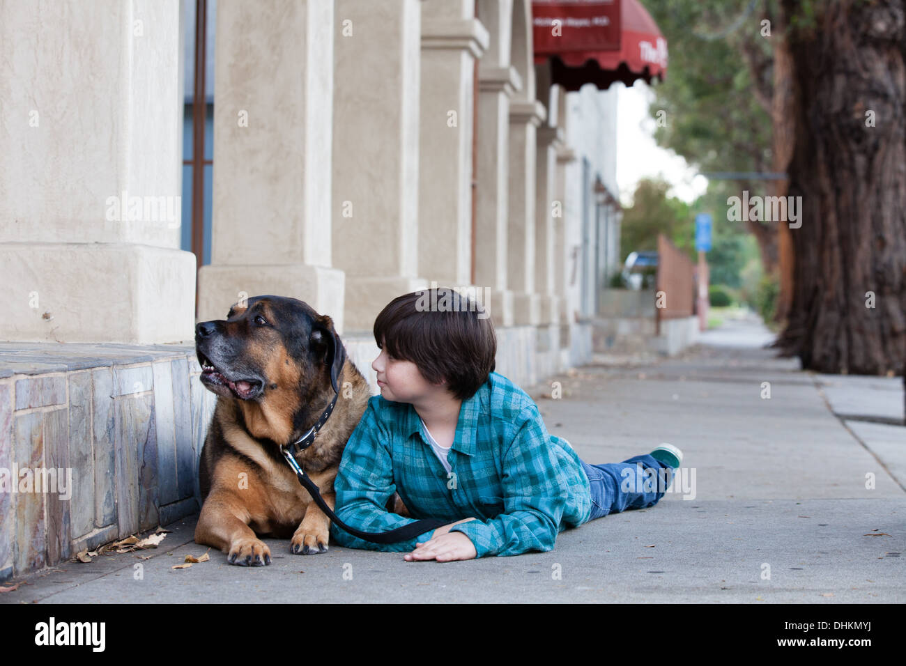 A 10 year old boy and his dog lying down on the sidewalk - Stock Image