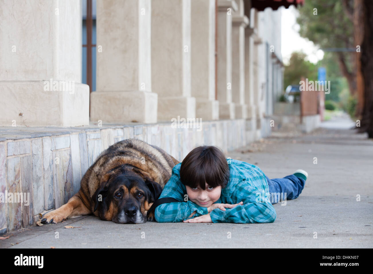 A  cute 10 year old boy and his dog lying down on the sidewalk - Stock Image