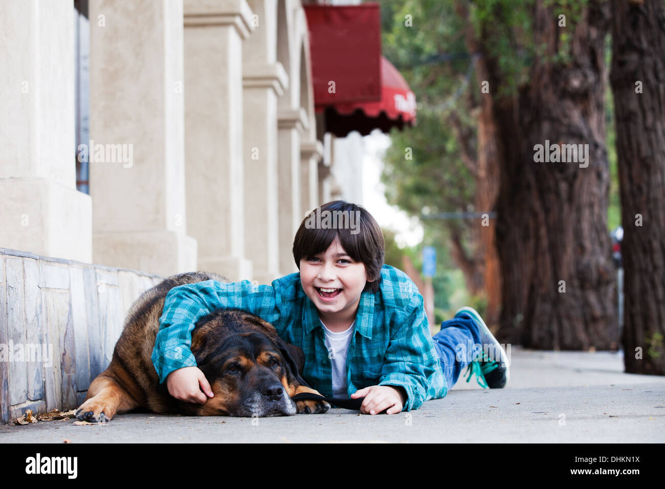A  cute 10 year old boy and his dog lying down on the sidewalk laughing - Stock Image