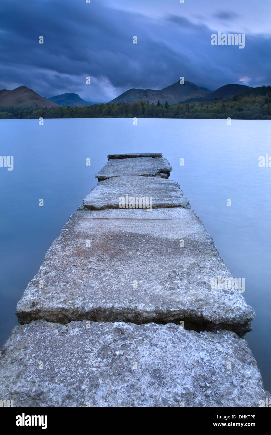 At dusk, the clouds were rolling in adding an eery feel across Derwent Water, Cumbria with a delapidated concrete Stock Photo