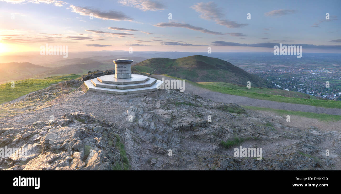 The Toposcope on the Worcestershire Beacon signifies the highest point on the Malvern Hills and is sidelit by the spring sunset - Stock Image