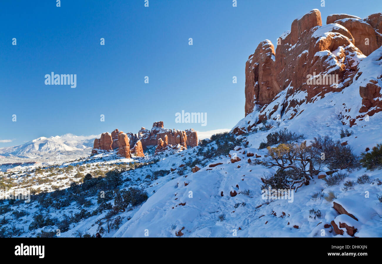 A snow-covered mound of red rock fins on the primitive loop trail in the Windows section of Arches National Park in Utah - Stock Image