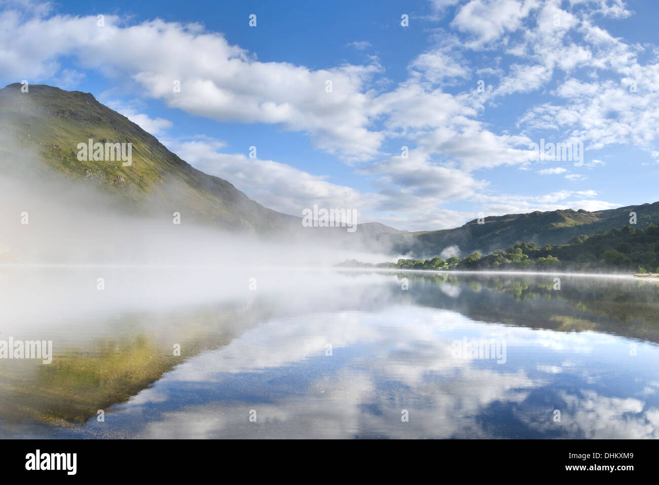Gallt y Wenallt and clouds being reflected into Llyn Gwynant. The mist rising over the lake obscures the Llyn Gwynant Stock Photo