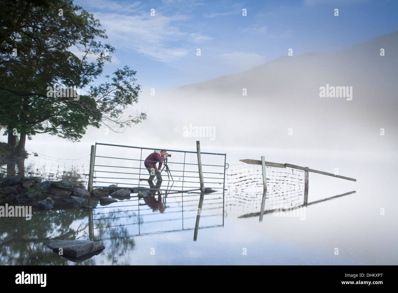 Photographer in a red coat taking a photograph of a fence and reflection going into Llyn Gwynant, Snowdonia, Wales. Stock Photo