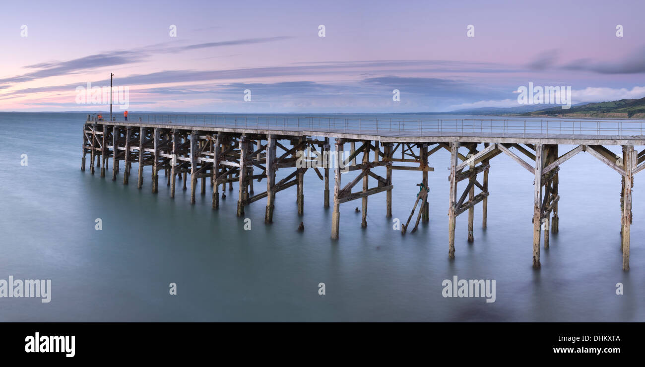 Two fishermen fishing from the collapsing pier at Trefor, Gwynedd, Wales at sunset. Stock Photo