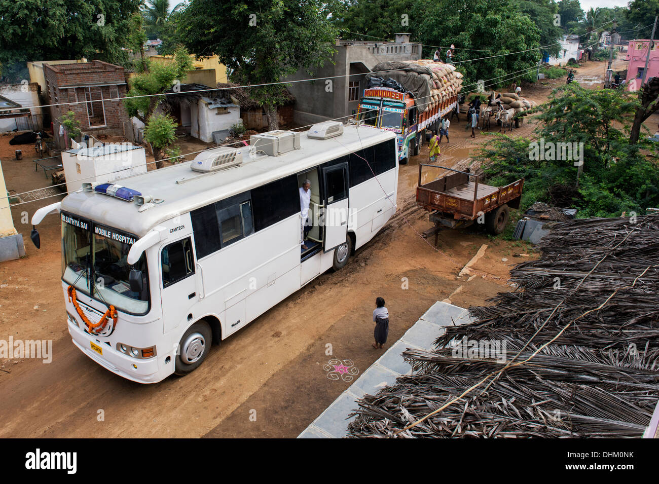 Sri Sathya Sai Baba mobile outreach hospital service clinic bus arriving at a rural Indian village. Andhra Pradesh, India - Stock Image